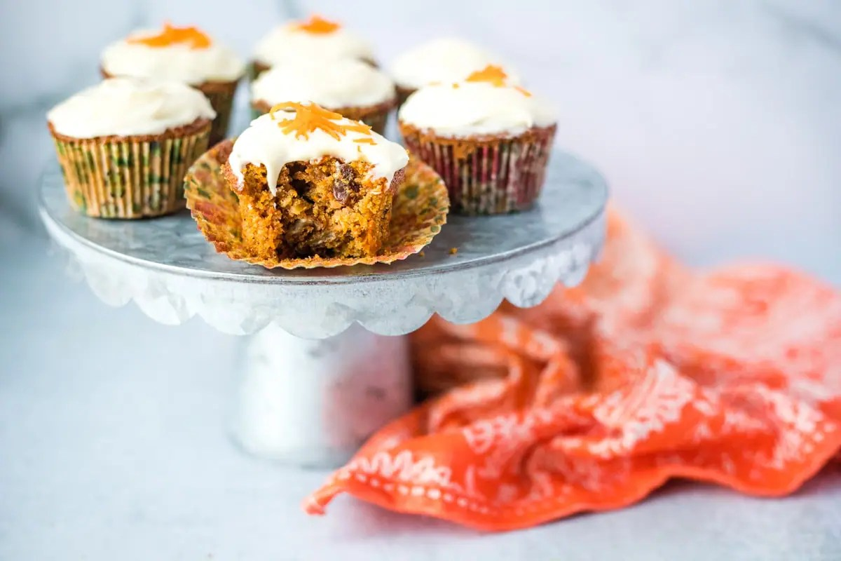 silver cake stand with carrot muffins and an orange linen