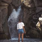 cold-water-therapy-woman-standing-beneath-waterfall
