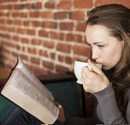 Does God exist - Photo of a young woman, drinking a cup of coffee and reading the Bible, to learn about a relationship with God.