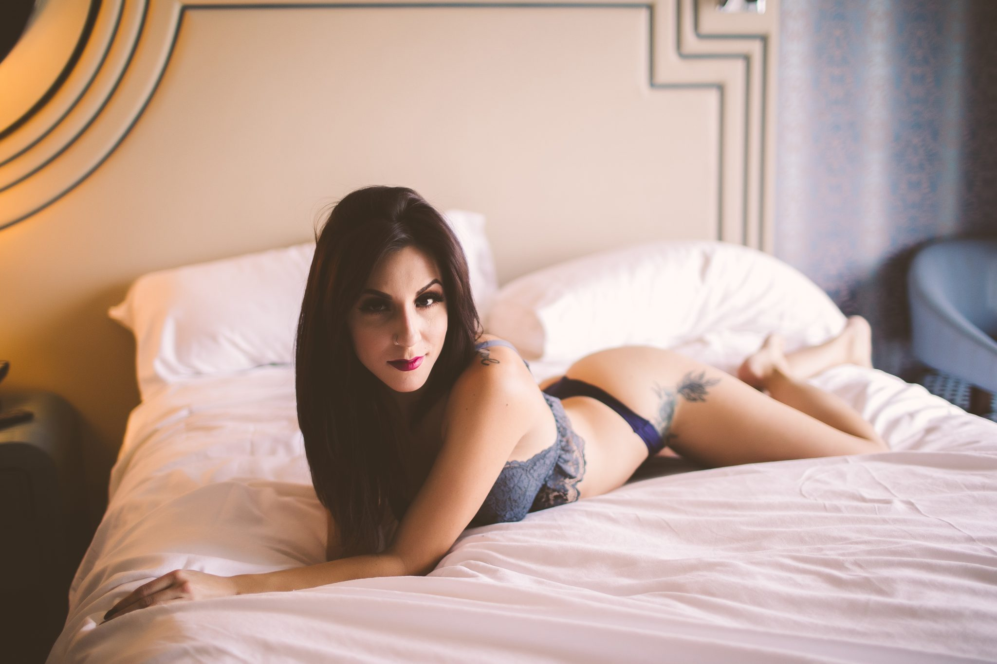 Tattooed model laying on a bed