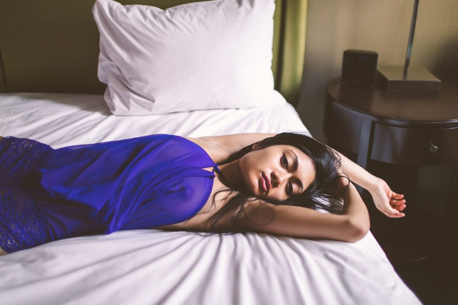 A woman posing on a bed in blue lingerie