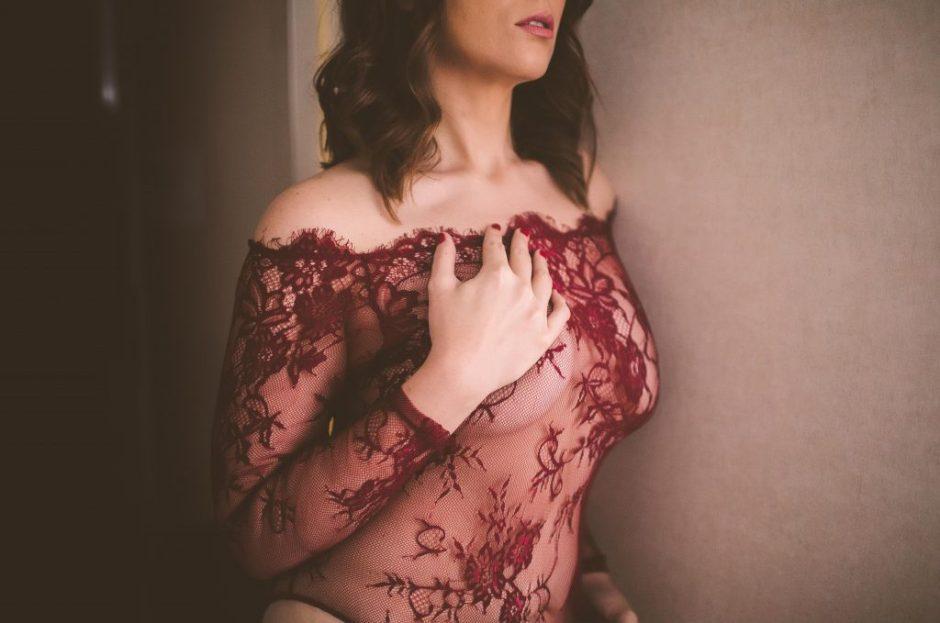 Sexy boudoir model posing in red lingerie