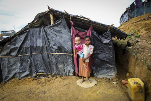 """Razia*, one year-old, and Selim*, six years-old, children of Nazrin*. They fled Myanmar when their village was attacked and are now living in a makeshift camp in Cox's Bazar district, Bangladesh.  In their mother Nazrin's* words:  """"The military came and burnt our house. They burnt everything. We were forced to leave Myanmar and come to Bangladesh. We had no other option. Now I feel secure at the makeshift camp because no one is burning down houses, no one is shooting anyone. It is safe. We feel secure here. All my children are now happy and safe. Before they weren't safe, but now we have peace."""""""