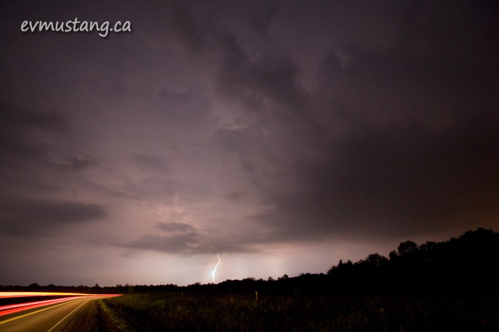 image of tail lights driving into lightning storm