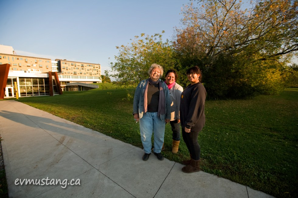 image of Muriel Miguel, Murielle Borst-Tarrant and Josephine Torrent outside Nozhem: First Peoples' House of Learning, Trent University, Peterborough