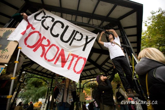 image of occupy toronto banner being hung in st. james park