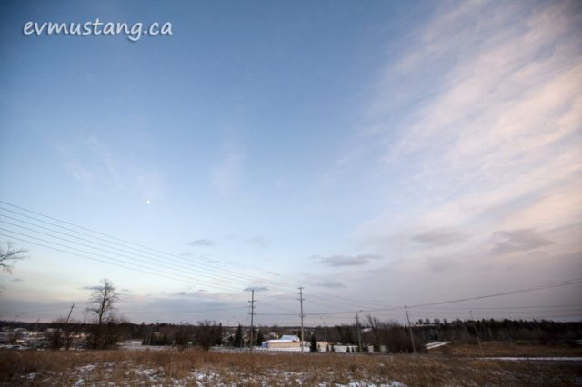 image of the moon rising over the snowy peterborough outskirts