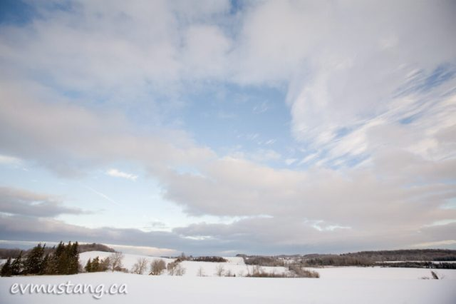 image of snow covered field under clouds and blue sky