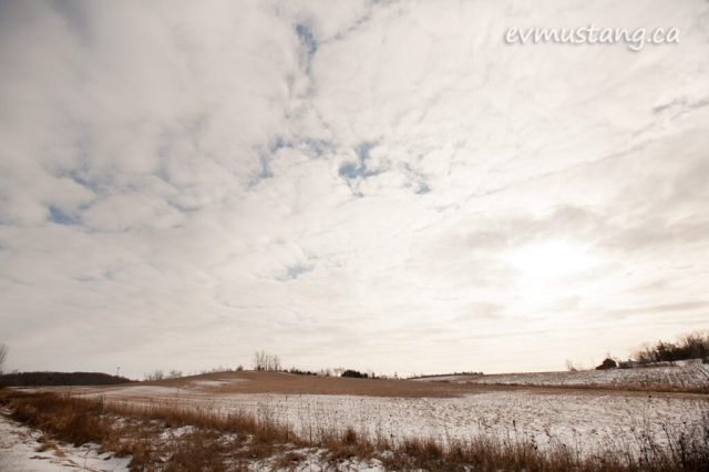 image of winter field with bright sun shining through blotchy white clouds