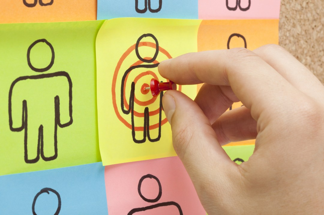 finding the target market - photo of pinning a target on post-it note character