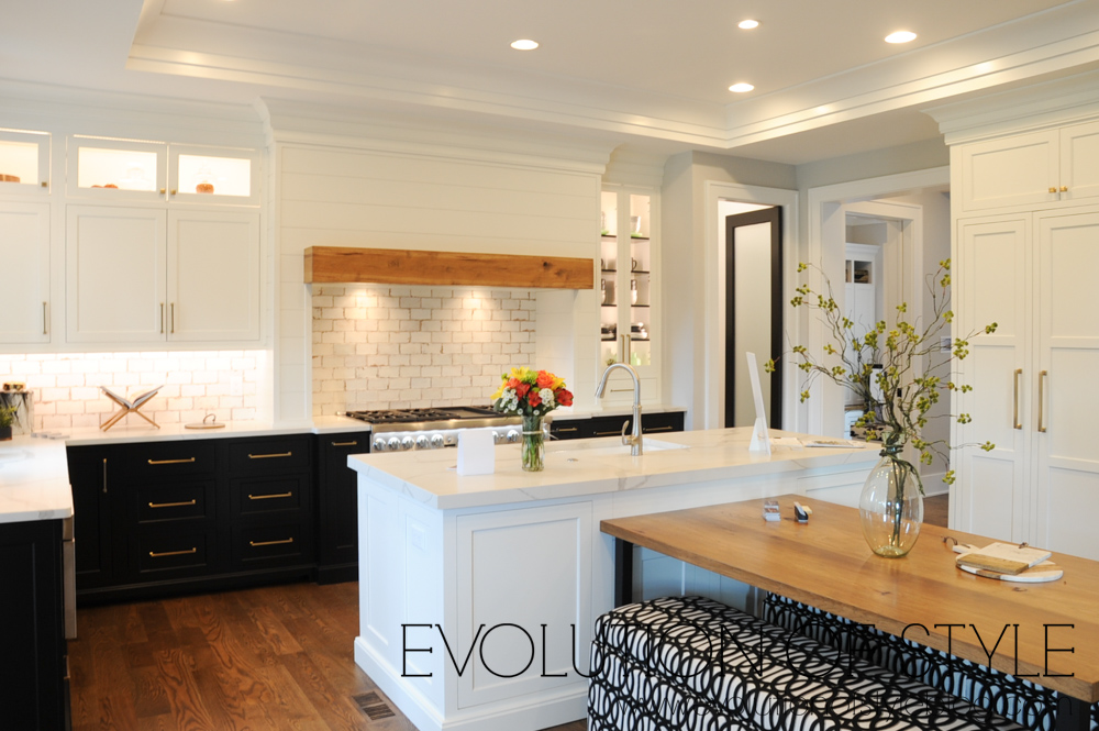 White upper cabinets with black lower cabinets and gold hardware