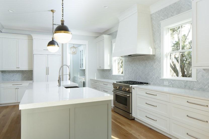 White kitchen with gray island and pendant lights
