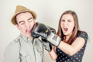 Frau schläft Mann mit Boxhandschuh in das Gesicht