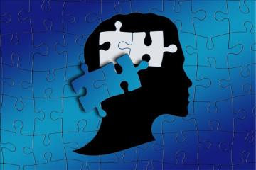 Puzzle mit Menschenkopf im Profil, wo zwei Puzzleteile dort fehlen, wo das Gehirn ist