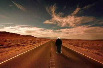 Wüstenlandschaft mit Straße, auf der eine Person mit Rollator läuft