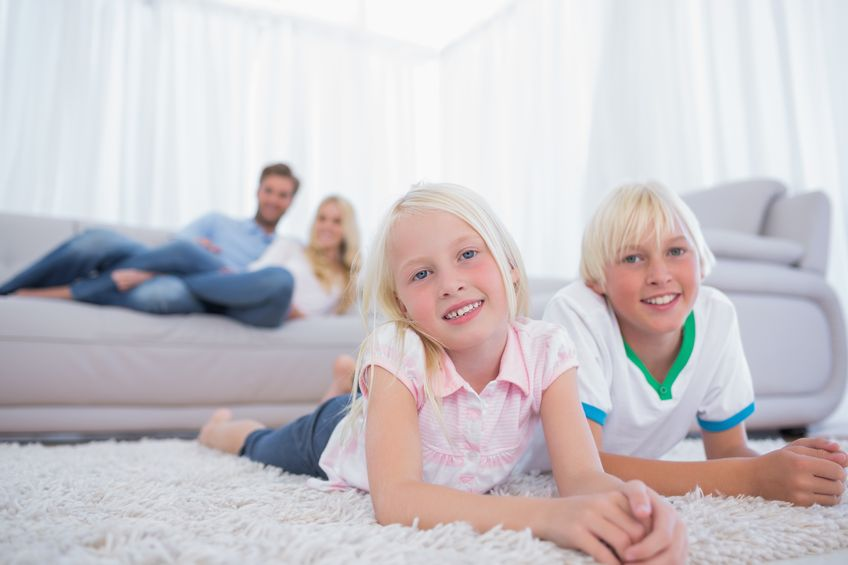 20635091 – children lying on the carpet and smiling at camera