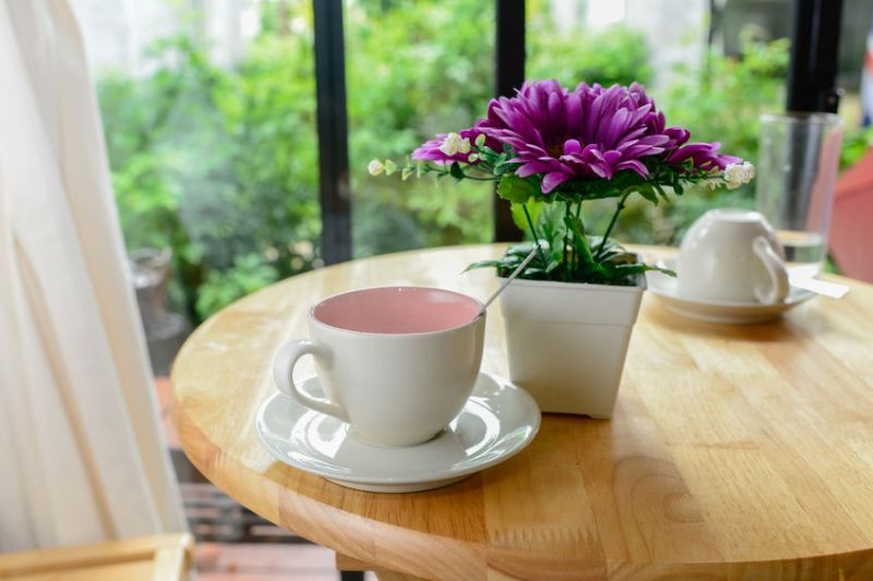 33744650 – coffee mug and flower pot on wooden table.