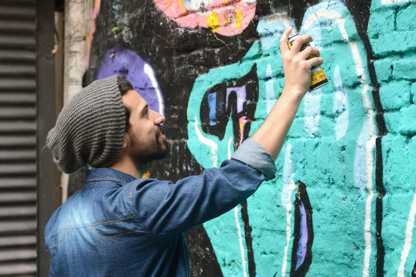 46044444 - young urban latin painter drawing a graffiti on the wall.