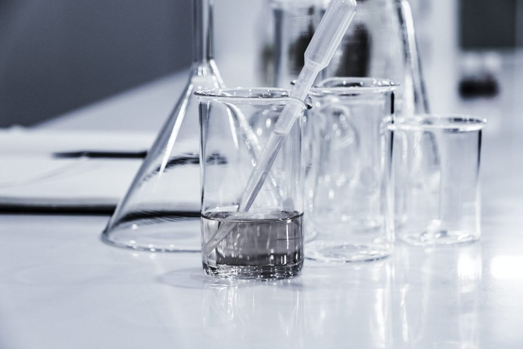 An image of conical flasks and beakers in a science lab.