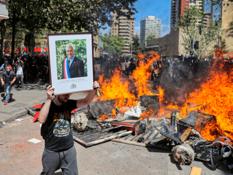 A demonstrator in Santiago, Chile, holds a picture of Chilean president, Sebastian Pinera, on 22 October 2019, during a protest against the country's state economic model. Photo: CNS/Reuters