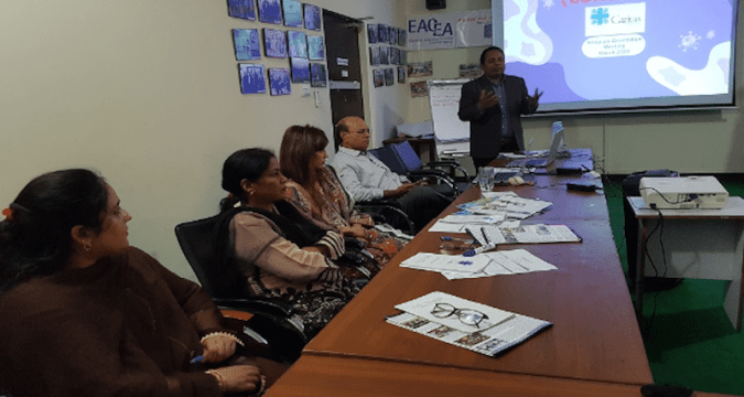 Nadeem Yousaf, standing, national humanitarian coordinator for Caritas Pakistan, briefs staff about the response to the Covid-19 outbreak. Photo: UCAN/Kamran Chaudhry