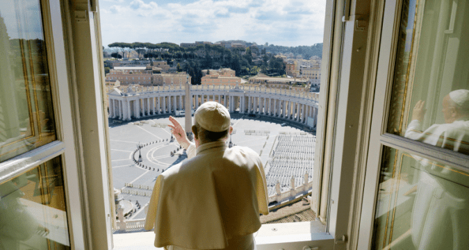 Standing in the window of the library of the Apostolic Palace overlooking an empty St. Peter's Square, Pope Francis blesses the city of Rome on March 15. Photo: CNS/Vatican Media via Reuters