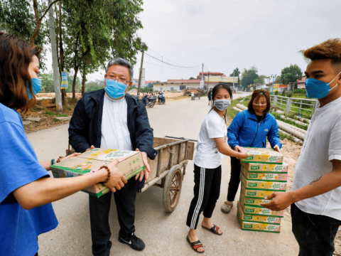 Father Francis Xavier Nguyen Duc Dai of Son Loi, Vietnam, distributes food to local people while wearing a protective mask. The area has been quarantined due to the Covid-19 coronavirus. Photo: CNS/Reuters