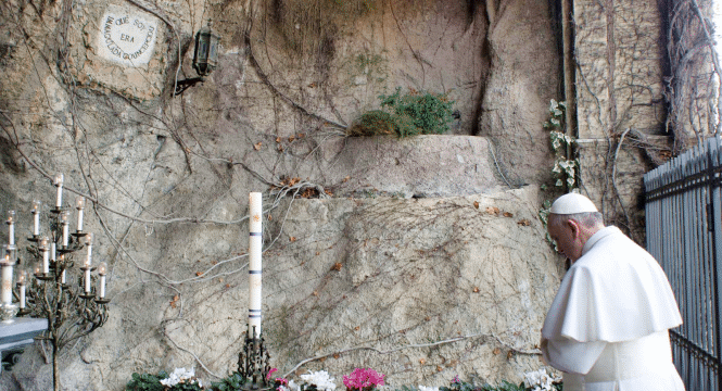 Pope Francis prays at a replica of the Lourdes Grotto in the Vatican Gardens. Photo: CNS/L'Osservatore Romano