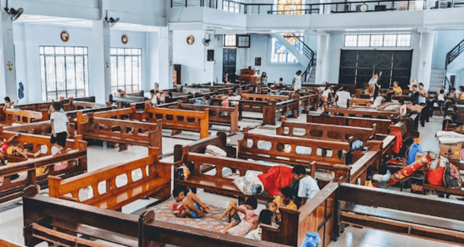 Evacuated families take shelter at Our Lady of the Pillar Church in Pilar, in Sorsogon, after being forced out of their homes by Typhoon Vongfong. Photo: UCAN/ courtesy of Father Treb Futol