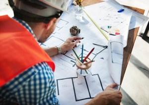Man wearing white hard hat leaning on table with sketch plans; Credit: Photo by rawpixel.com from Pexels