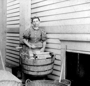 In this vintage photo, a washerwoman looks resigned to her onerous task.