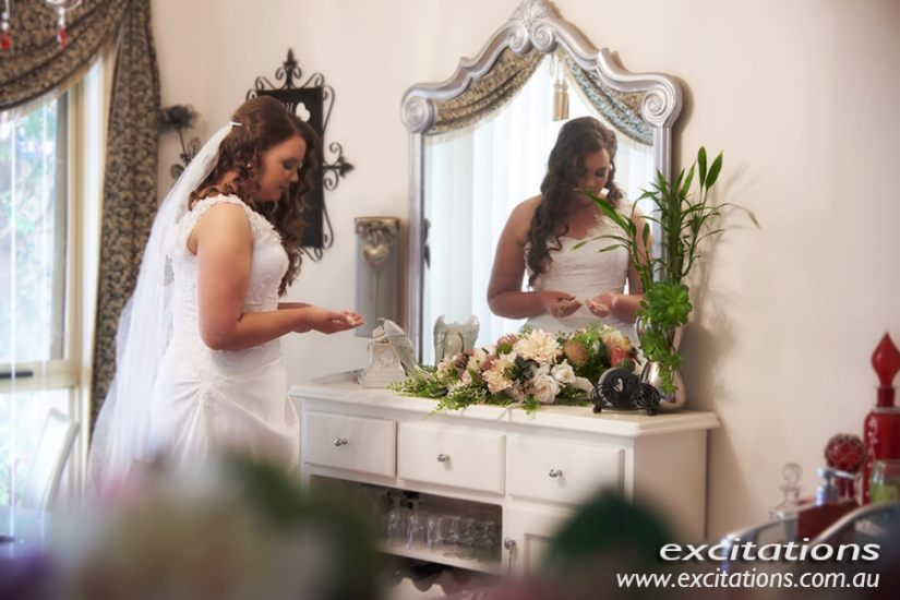 half length bride at dressing table in front of mirror preparing for her wedding photography. Wedding photography Mildura by Excitations.