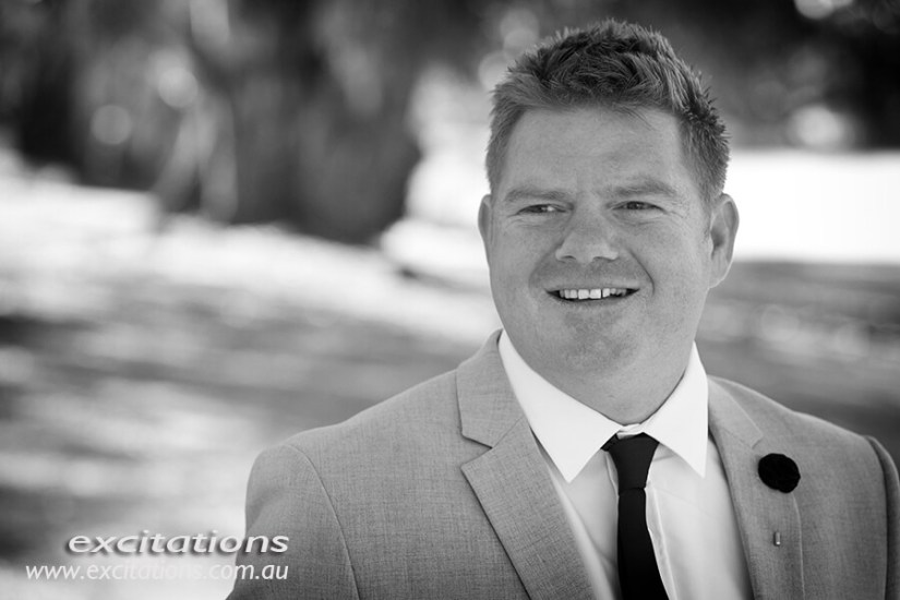 Closeup black and white photograph of groom on his wedding day, outdoors. Wedding pictures in Mildura by Excitations.