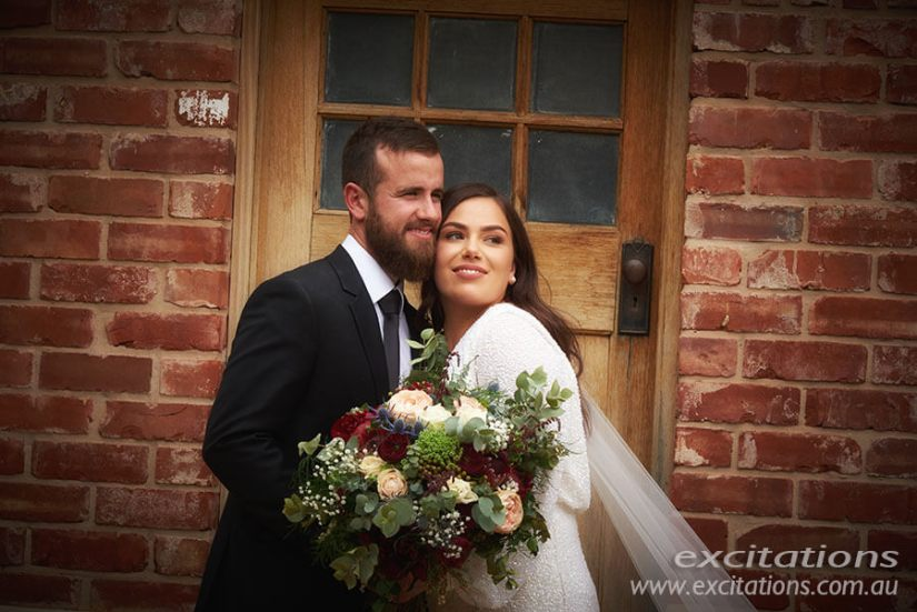 Half length of bride and groom in front of brick wall. Mildura wedding photography by Excitations.