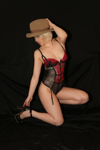 Courtney wearing a hat with a skimpy body with suspenders