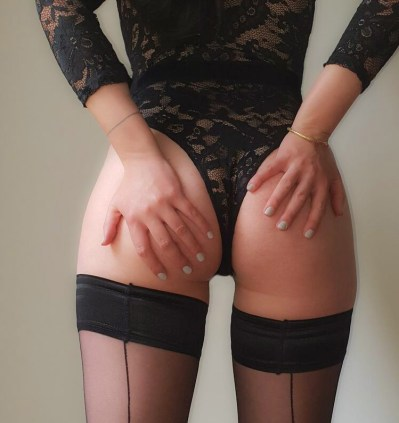 Woking Escort Molly with her hands on her perfect bottom. Surrey massage