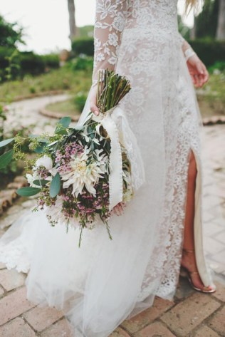 Bride with bouquet and white lace bridal gown