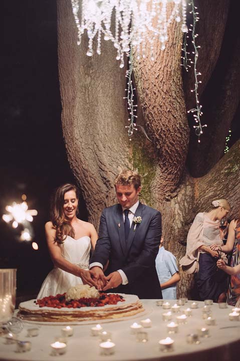 Cutting of the cake under a tree at Tuscan wedding dinner