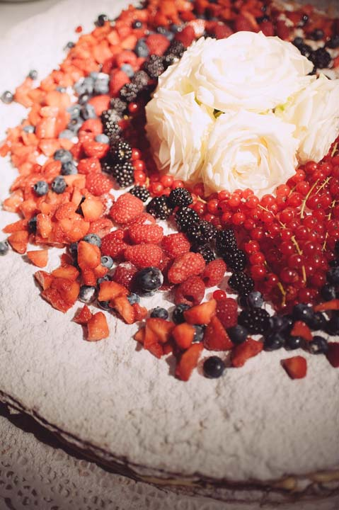 Wedding cake with fresh berries and white roses