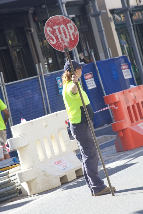Traffic attendant holding up a stop sign in the city