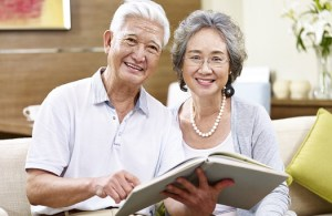 senior asian couple sitting on couch holding a book looking at camera smiling