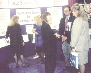 E. Jane Lorimer conversing at TSB booth during a past EXHIBITOR Show