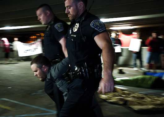 Bloomington police arrest protester Cooper Childers Monday night in the parking garage at Fourth and Walnut streets. David Snodgress | Herald-Times