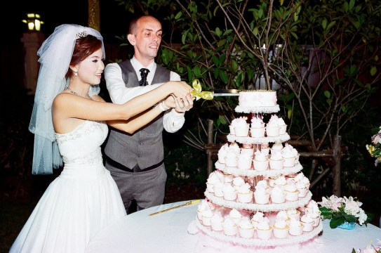 A Western man and Thai woman cutting the cake on their wedding day.