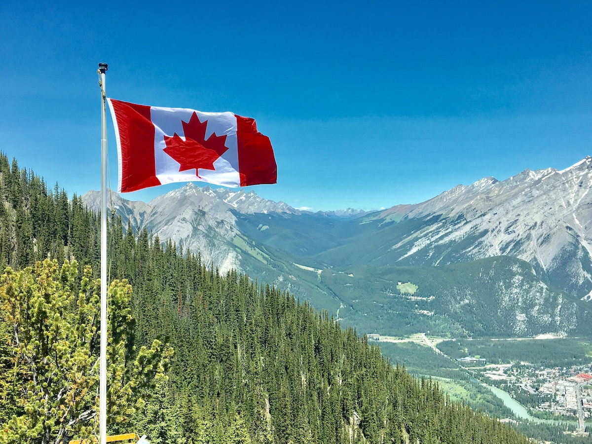 The Canadian flag flying above mountains in Canada.