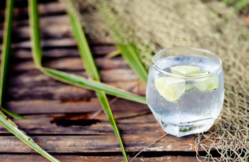Gin tonic in glass with ice and lime slice and frangipany flower on a wooden background