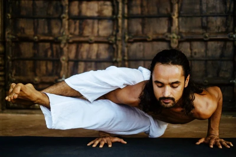 Young athletic Indian man doing yoga in front of old antique wooden door