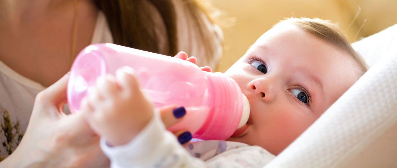 Babykostwärmer: Baby trinkt aus warmer Flasche