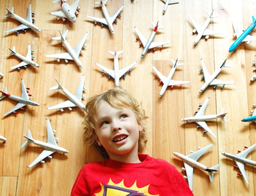 A boy surrounded by toy planes