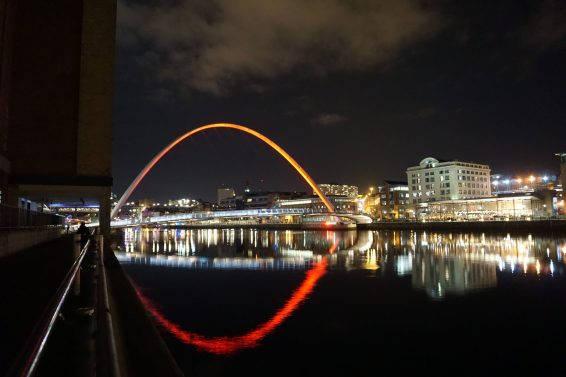 Millennium bridge at night in Newcastle, with lights reflected off the water.